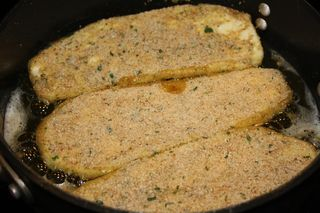 Frying long slices of breaded eggplant